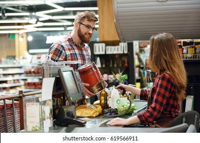 Photo of happy young man standing near cashier's desk in supermarket shop with beer. Looking aside.