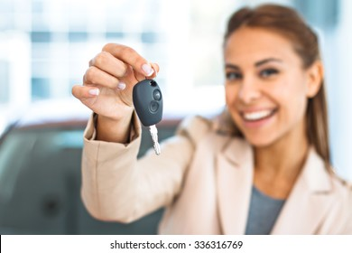 Photo of happy young mixed race woman showing key to her new car. Concept for car rental. Focus on key