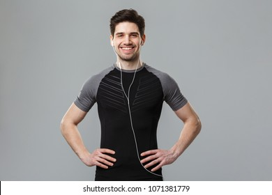 Photo of happy young sportsman standing isolated over grey wall background looking camera listening music with earphones.