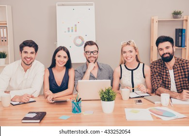 photo of  happy young team of  businesspeople sitting at conference table smiling