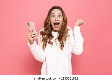 Photo of happy young woman with beautiful long hair screaming and clenching fist while holding mobile phone in hand isolated over pink background