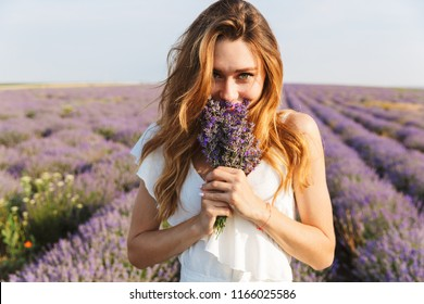 Photo of happy young woman in dress holding bouquet with flowers while walking outdoor through lavender field in summer