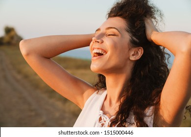 Photo of happy young woman grabbing her head and smiling while walking in countryside during sunny day