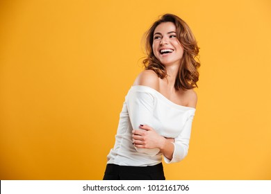 Photo of happy young woman isolated over yellow background. Looking aside.
