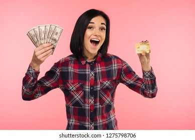Photo of happy young woman standing isolated over pink background. Looking at camers holding money and credit card. - Image