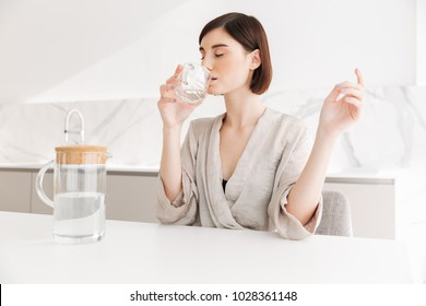 Photo of healthy brunette woman waking up in morning and drinking still fresh water from transparent glass in white flat