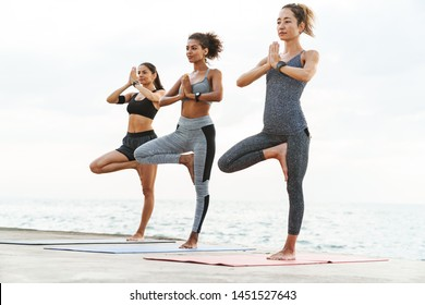 Photo of healthy multiethnic sportswomen in tracksuits doing exercises with palms together on yoga mats by seaside in morning