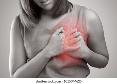 The photo of heart is on the woman's body, Severe heartache, Having heart attack or Painful cramps, Pressing on chest with painful expression.