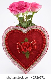Photo of a heart shaped box of chocolates with four pink roses behind it