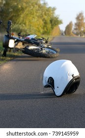 Photo of helmet and motorcycle on road, the concept of road accidents