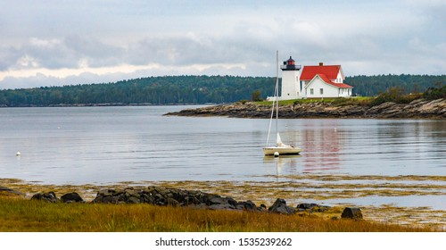 Photo of Hendricks Lighthouse in Southport Maine on a cloudy day.  The lighthouse is not far from Boothbay Harbor, Maine.