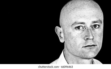 photo high contrast dark moody male in his 30's in shirt on black back drop