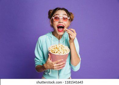 Photo of hipster girl 20s in sunglasses screaming and holding bucket with popcorn isolated over violet background in studio
