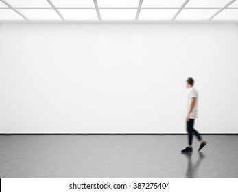 Photo of hipster in modern gallery looking at the empty canvas. Blank mockup, motion blur
