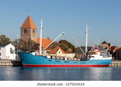 Photo of a historic coaster of the Danish class called Caroliner lyiung in the Harbour of Stege at the Island Moen with the main church of the village in the background