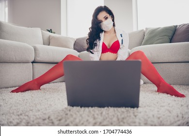 Photo of horny lady remote porn worker home online laptop chat play naughty nurse prostitute role look screen touch herself between legs show client secret place sit floor wear bikini flu mask indoors