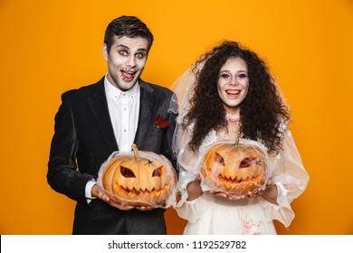 Photo of horrific zombie couple bridegroom and bride wearing wedding outfit and halloween makeup holding carved pumpkin isolated over yellow background