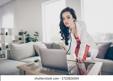 Photo of hot sexy tempting lady work home remote online notebook chat play naughty nurse role listen stethoscope heart beating client bend chest to screen wear lab coat red bikini indoors