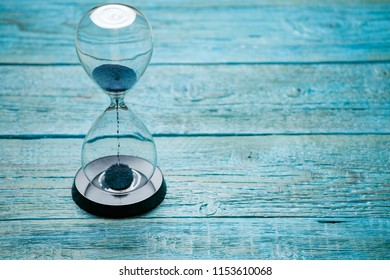 Photo of hourglass with blue sand on wooden background,