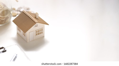 Photo of house model, clipboard, saving money in vase putting together on white table. Planning for buying a house concept.