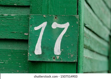 Photo of house number on a green wooden wall