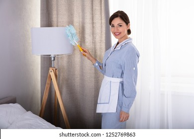 Photo Of Housemaid Cleaning Lamp With Feather Duster