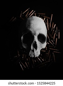Photo of a human skull laying on a pile of gun shells on black background.