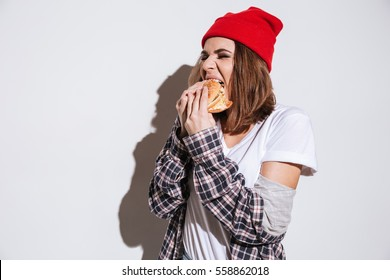 Photo of hungry young woman dressed in shirt in a cage print wearing hat standing isolated over white background and eating burger
