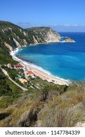 Photo of iconic beach of Petani with rocky steep cliffs and beautiful turquoise wavy sea and sunbeds, Cefalonia island, Ionian, Greece