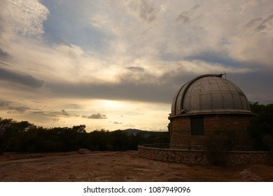 Photo of iconic observatory of Athens in Philopapos hill at sunset with beautiful clouds and colours, Athens historic center, Attica, Greece