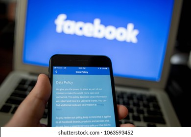 In a photo illustration, a screen from the Facebook app is seen on an iPhone in front of a Facebook logo, April 7, 2018.
