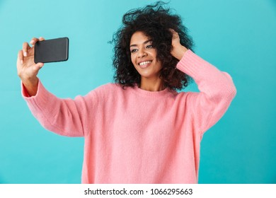 Photo of image beautiful woman making selfie on her cell phone with smile isolated over blue background