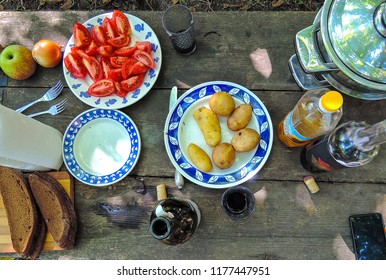 photo image of country dinner at the wooden table with vegetables and wine in summer time