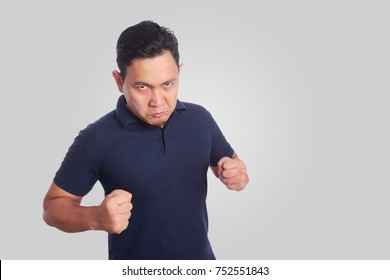 Photo image of funny Asian man showing synical unhappy angry mad punching fighting facial expression