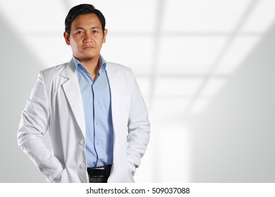 Photo image of a handsome, attractive, confident, successful young Asian male doctor smiling to the front with blurred, out of focus background