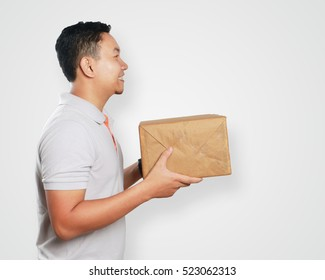 Photo image portrait of a cute handsome young Asian courier man smiling while giving gift package box in delivery duty