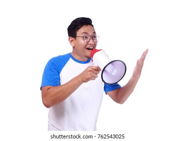 Photo image portrait of funny young attractive Asian man shouting with megaphone, happiness excited calling people promotion concept, isolated on white