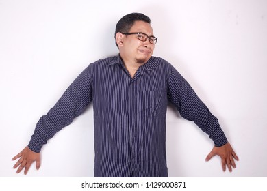 Photo image of young funny Asian man afraid expression, being pushed to the wall, surrender gesture against white background