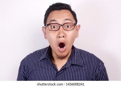 Photo image of young funny Asian man shocked or surprised expression with mouth open, against white background