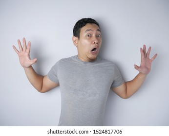 Photo image of young funny Asian man afraid expression with hands raised up, surrender gesture, while standing against grey wall