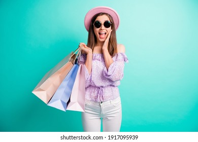Photo of impressed brunette girl hold bags open mouth hand face wear purple shirt cap trousers spectacles isolated on blue color background