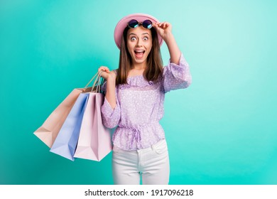Photo of impressed brunette girl hold bags take off spectacles wear purple shirt cap trousers isolated on blue color background