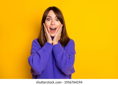Photo of impressed young girl hands on cheeks open mouth staring camera isolated on yellow color background