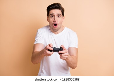Photo of impressed young guy gamer open mouth yelling excited game isolated on beige color background