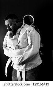 Photo of a insane man in his forties wearing a straitjacket leaning up against an asylum door.