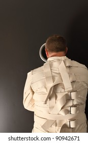 Photo of a insane man in his forties wearing a straitjacket looking out the hole of an asylum door.