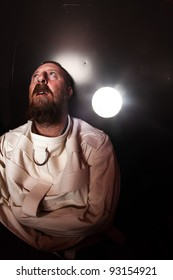 Photo of an insane man in his forties wearing a straitjacket standing in a cell of an asylum with the light from the hallway streaming in.