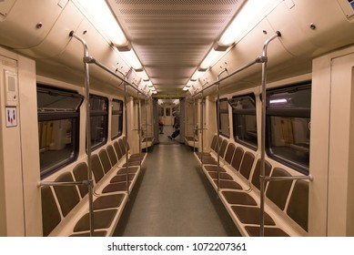 Photo inside the subway train car with confused seats without passengers