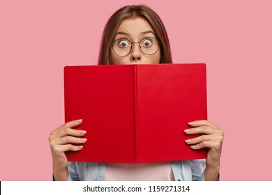 Photo of intelligent female student covers face with red book, stares at camera with bugged eyes, feels shocked to hear sudden news, cramms for exam at college, isolated over pink background