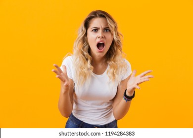 Photo of irritated woman in casual clothes shouting in anger isolated over yellow background